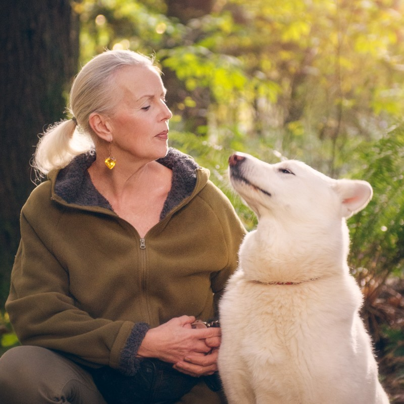 Photo of a woman and her pet dog a white german shepherd in a wooded park